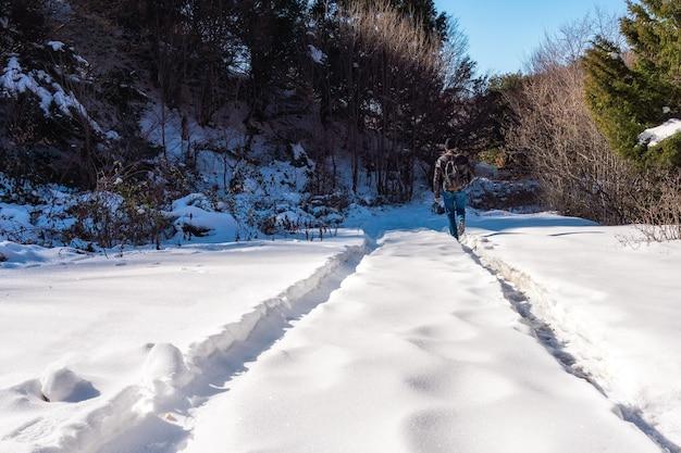 バックパックを背負ったハイカーが雪道をハイキングに行く
