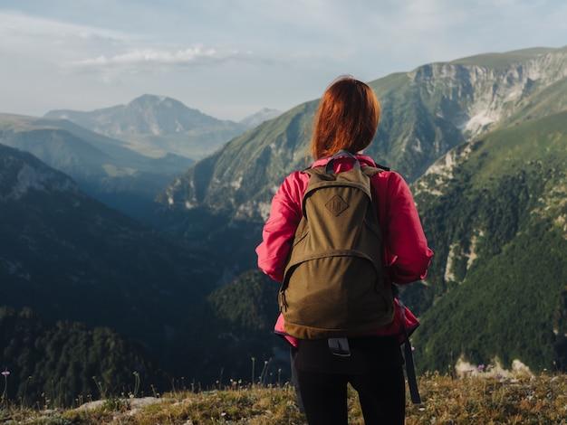 自然の山の中でバックパックとピンクのジャケットのレギンスを持ったハイカー。高品質の写真