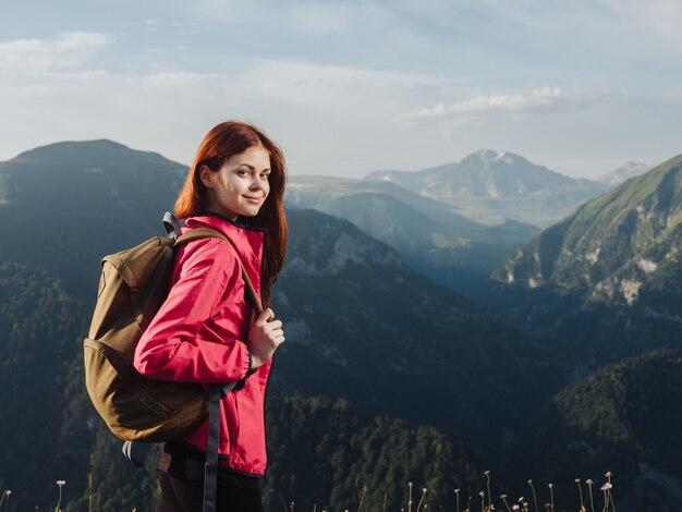 자연의 산에서 배낭과 핑크색 재킷 레깅스를 가진 등산객