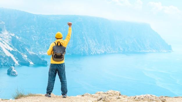 여름에 바다의 아름다운 전망을 감상할 수 있는 산꼭대기에 손을 들고 배낭을 메고 있는 등산객. 여행 컨셉