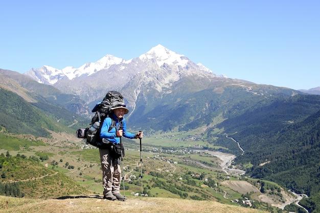 배낭과 트레킹 스틱이 산 풍경 표면에 서있는 등산객