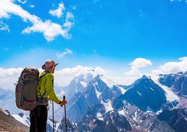 Путешественник с рюкзаком на вершине скалы