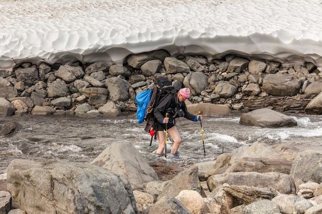 Hiker with backpack crosses cold creek. on a trekking tour in sarek