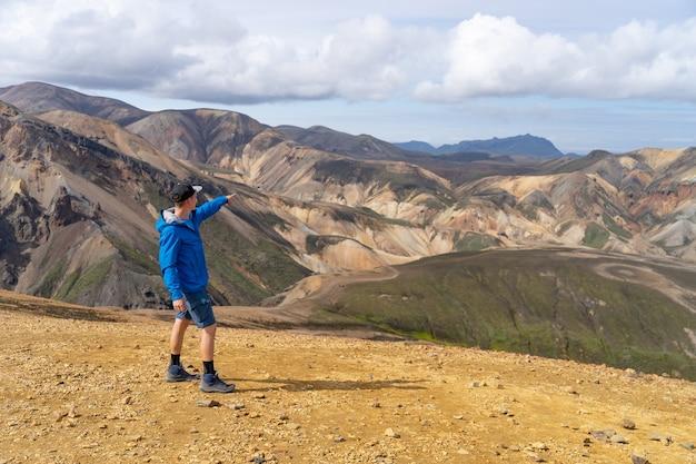 Путешественник с рюкзаком в долине ландманналаугар. исландия. красочные горы на туристической тропе лаугавегур