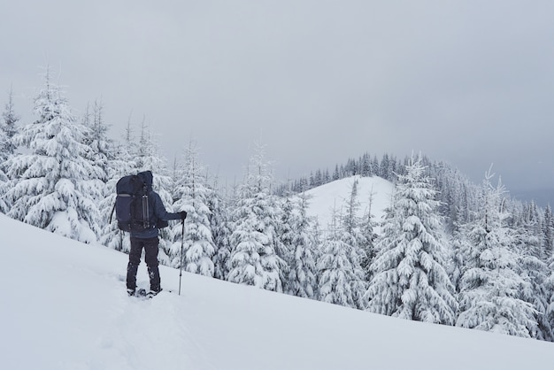 Hiker, with backpack, is climbing on the mountain range, and admires snow-capped peak. epic adventure in the winter wilderness