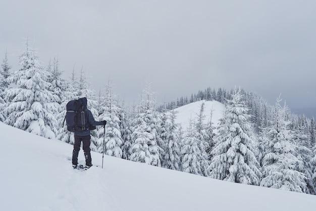Путешественник, с рюкзаком, поднимается по горной цепи и любуется заснеженной вершиной. эпическое приключение в зимней глуши