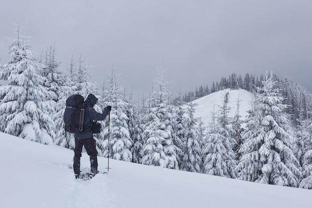 Путешественник с рюкзаком поднимается по хребту и любуется заснеженной вершиной. эпическое приключение в зимней глуши.