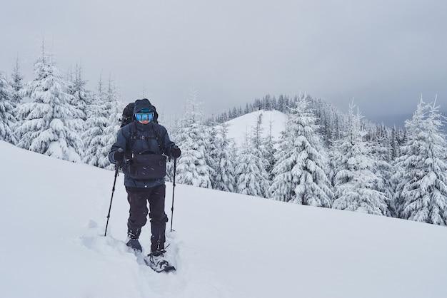バックパックを背負ったハイカーは山脈に登り、雪をかぶった山頂を眺めています。冬の荒野での壮大な冒険。