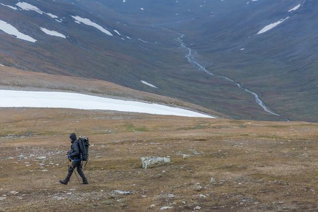 Hiker with backpack at kungsleden trail admiring nature of sarek
