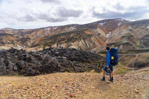 ランドマンナロイガル渓谷を見ているバックパックを持ったハイカー。アイスランド。ロイガヴェーグルのハイキングコースにある色とりどりの山々。マルチカラーの岩、鉱物、草、苔の層の組み合わせ。