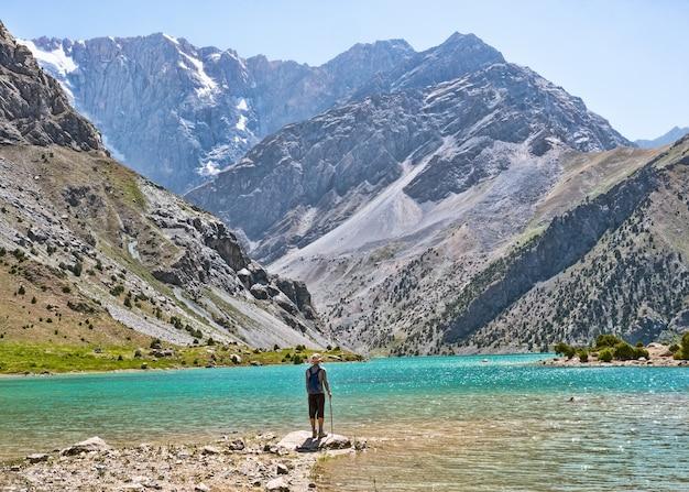 Путешественник с рюкзаком возле озера куликалон на фоне скалистых гор. фанские горы, таджикистан, средняя азия
