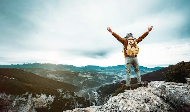 배낭이 산 꼭대기에 팔을 올리는 등산객-승리를 축하하는 성공적인 남자