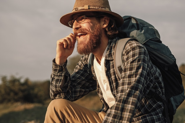 Hiker with backpack smiling and looking away while resting