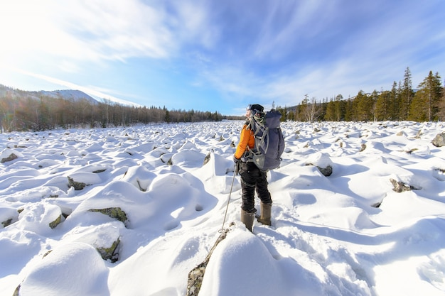 Hiker with backpack on the snow field of stones at the way to the rocky mountains