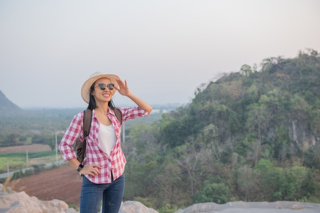 Путешественник с рюкзаком стоит на вершине горы и наслаждается прекрасным видом на долину