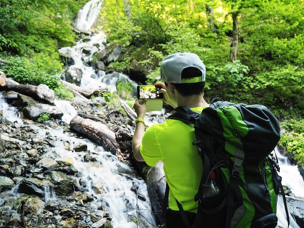 晴れた夏の日にスマートフォンで滝の写真を撮るバックパックとハイカー