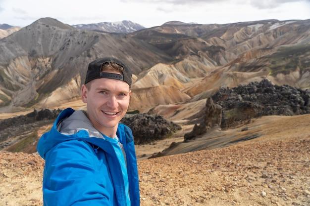 ランドマンナロイガル渓谷で自分撮りをするバックパックを持ったハイカー。アイスランド。ロイガヴェーグルのハイキングコースにある色とりどりの山々。マルチカラーの岩、鉱物、草、苔の層の組み合わせ。