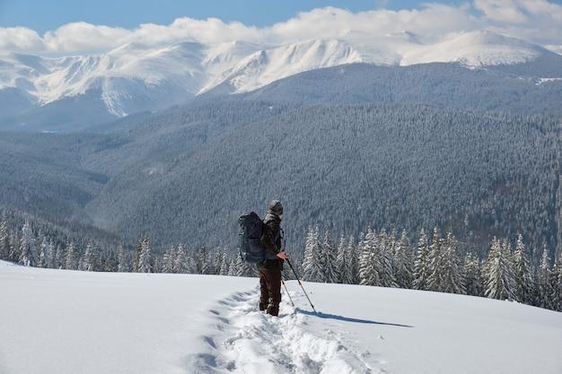추운 겨울 날 눈 덮인 산비탈을 걷고 있는 배낭을 메고 등산객.