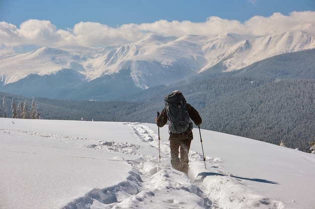 寒い冬の日に雪山の丘の中腹を歩くバックパックを持ったハイカー。