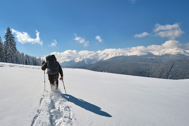 Hiker with backpack walking on snowy mountain hillside on cold winter day.