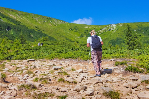 Hiker with backpack walks on rocky terrain while climbing a mountain