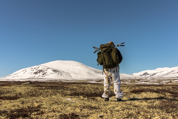 Hiker with big backpack walking in winter mountains in dovre, norway. right side