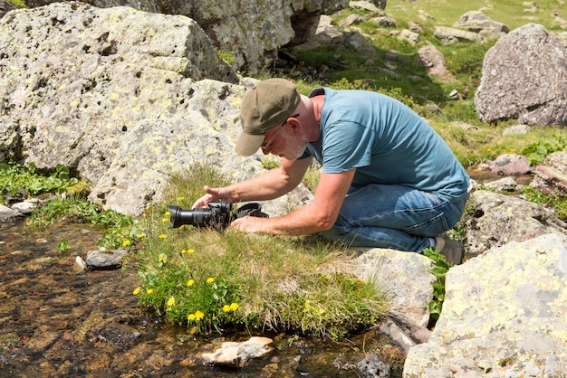 Hiker with camera taking picture of small stream