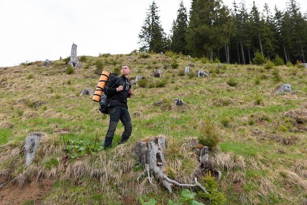 装備のあるハイカーは山でのハイキングに時間を費やしています