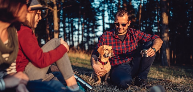 Hiker with friends and his dog resting and drinking coffee