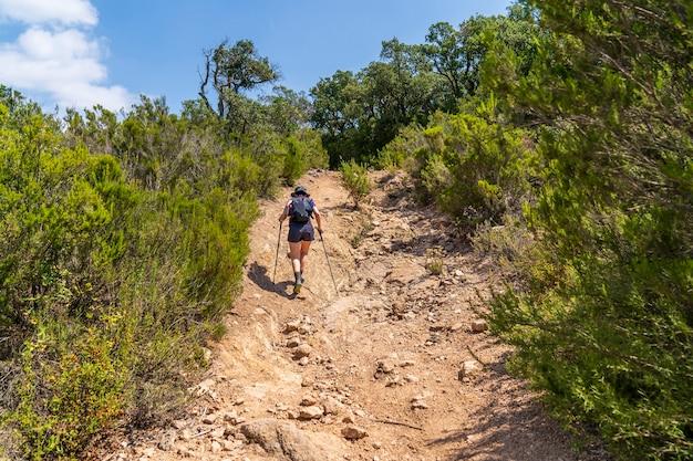 Hiker woman climbing a path through the