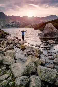 ハイカーの女性は素晴らしい風景を探索し、挙手で山の湖の近くの景色を楽しむ、ハイタトラ、ポーランド