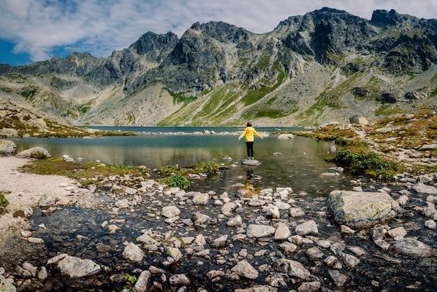 ハイカーの女性は素晴らしい山の風景を探索し、ジャケットを着た黄色のポプラズケプレソ湖の近くの景色を楽しんでいます