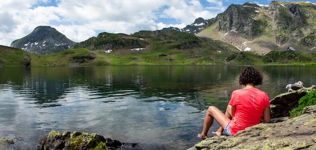 フランスのピレネー山脈の湖のほとりで休んでいるハイカーの女性
