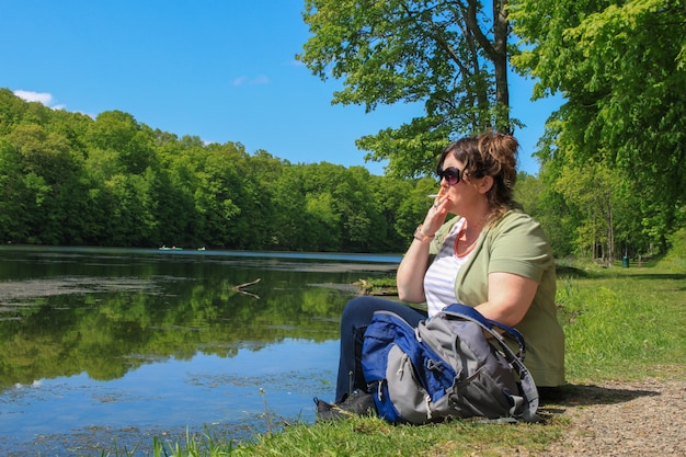 Hiker woman sitting on lake edge with backpack and smoking cigarette