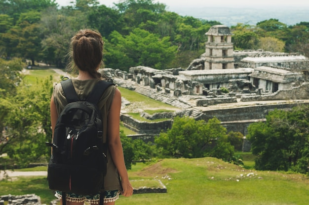 Путешественник женщина с рюкзаком, глядя на древние руины майя