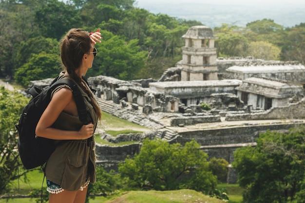 Путешественник женщина с рюкзаком, глядя на древние руины майя Premium Фотографии