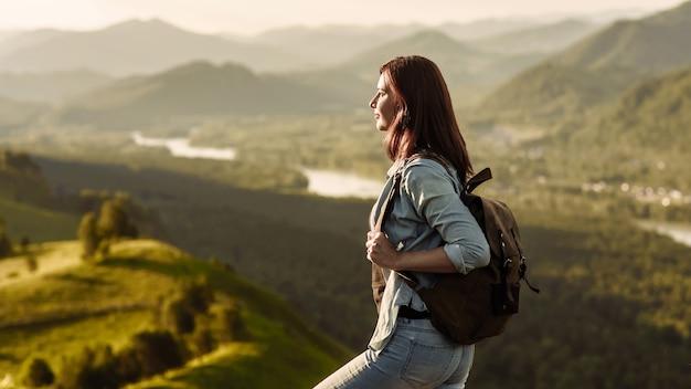 Путешественник женщина с рюкзаком в джинсовом костюме, глядя на заходящее солнце в горах. концепция путешествия и поездки