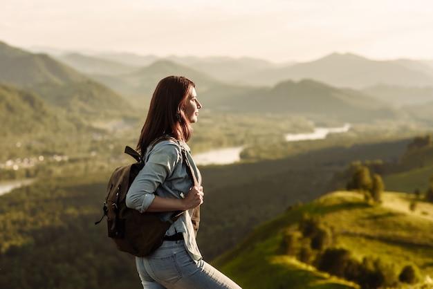 Турист женщина с рюкзаком в джинсовом костюме, глядя на заходящее солнце в горах.