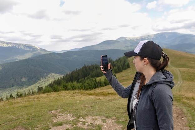 夏の山の美しい風景を写真に撮るバックパックを持つハイカー若い女性