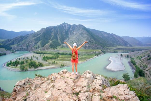 Женщина hiker распростертыми объятиями на вершине горы