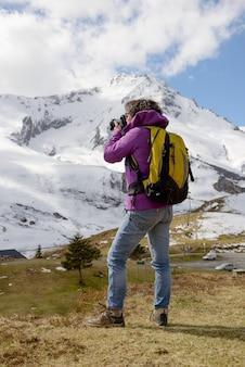 Hiker с камерой и рюкзаком фотографируя красивую гору
