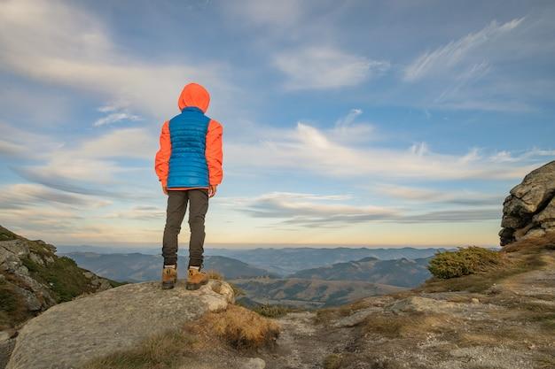Hiker мальчика маленького ребенка стоя в горах наслаждаясь взглядом изумительного ландшафта горы.