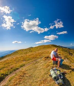 Мужской hiker стоя на вершине скалистый пик с видом на горный пейзаж.