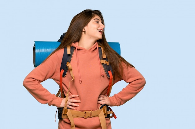Девушка hiker представляя с оружиями в бедре и смеясь над дальше на сини