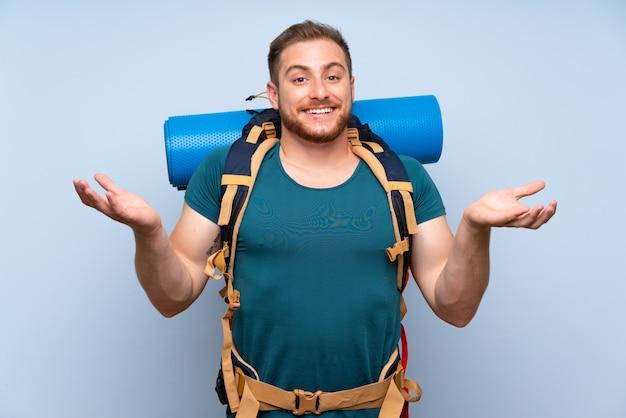 Человек hiker над голубой стеной с шокированным выражением лица