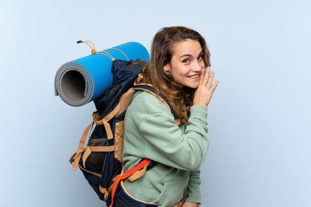 Молодая белокурая девушка hiker над изолированной голубой предпосылкой шепча что-то