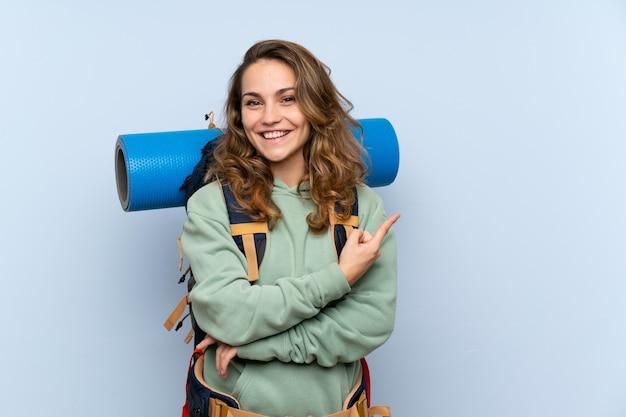Молодая белокурая девушка hiker над изолированной голубой стеной указывая к стороне для того чтобы представить продукт