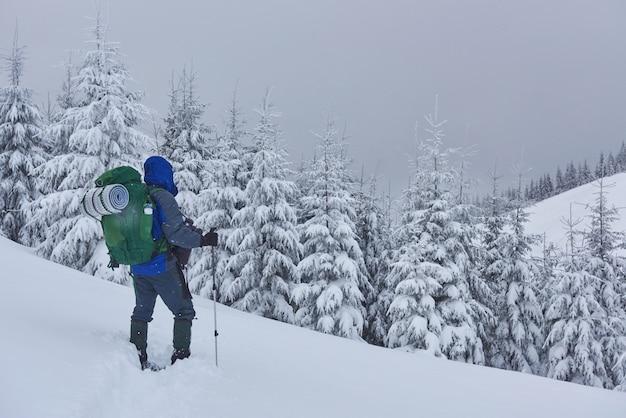 Hiker, с рюкзаком, поднимается по горной цепи и любуется заснеженной вершиной. эпическое приключение в зимней глуши