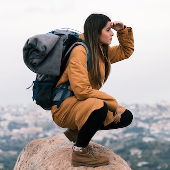 Молодая женщина hiker, сидя на вершине скалы с ее рюкзаком, экранируя глаза