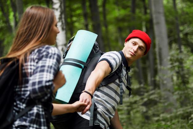 Человек hiker направляя женщину в лес, концепцию перемещения
